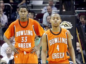 BGSU's Danny McElroy (33), left, stands on the court while teammates including Wiley Roberts (4), right, walk off after being defeated by Western Michigan.