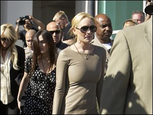 Lindsay Lohan leaves Los Angeles Superior Court, Thursday followed by her mother, Dina, far left, and sister, Ali, second from left.