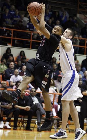 Scott's Dontonio Kynard pulls in a rebound Wednesday night in front of Defiance's Eric Stapleton.