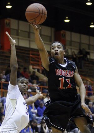 Damond Powell of Rogers goes to the basket against  Henry Newson of Waite in a Division II district semifinal Wednesday night at Anderson Arena. Powell led the Rams (13-5) with 19 points.