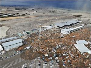 Tarmac, parking lot and surrounding area are covered with mud and debris carried by tsunami at Sendai Airport in Sendai, Miyagi Prefecture (state) after Japan was struck by a strong earthquake off its northeastern coast Friday, March 11, 2011.