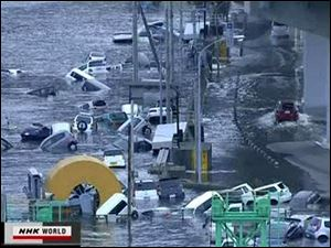 In this video image taken from Japan's NHK TV, cars are washed away in a coastal area of Kamaishi, Iwate prefecture Japan Friday March 11, 2011 following a massive earth quake.