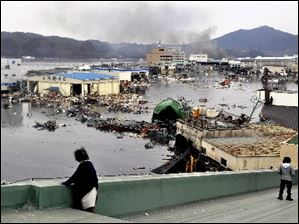 An earthquake-triggered tsunami washes away a warehouse and vehicles in Kesennuma, Miyagi prefecture (state), Japan, on Friday, March 11, 2011.