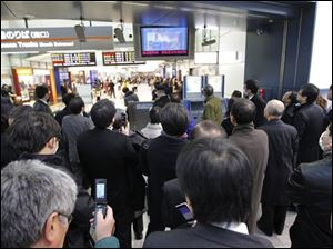 Train passengers watch TV at Tokyo's Shinagawa train station to get first-hand information on a very strong earthquake on Friday March 11, 2022. The quake unleashed a 13-foot (4-meter) tsunami that swept boats, cars, buildings and tons of debris miles inland.