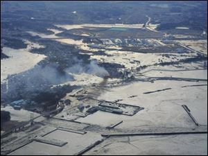 A smoke billows from a fire as an area of Soma port is flooded by waters after tsunami spawned by a powerful earthquake in Soma, Fukushima prefecture (state), Japan, Friday, March 11, 2011.