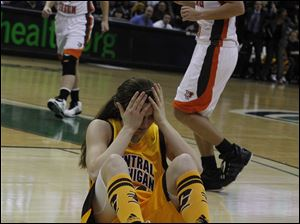 Central Michigan's Niki DiGuilio holds her head in pain after fouling a BGSU player.