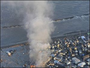 Smoke billows from residences on fire as a coastal area is flooded by waters after a tsunami in Iwaki, Fukushima prefecture (state), Japan, Friday, March 11, 2011.