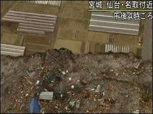 In this video image taken from Japan's NHK TV, houses, cars and debris half submerged is swept towards a highway, unseen, by a tsunami in the Sendai city area, Miyagi Prefecture (state) after Japan Friday March 11, 2011 following a massive earth quake.