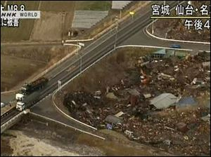 In this video image taken from Japan's NHK TV, houses, cars and debris half submerged is swept towards a highway by a tsunami in the Sendai city area, Miyagi Prefecture (state) after Japan Friday March 11, 2011 following a massive earth quake.