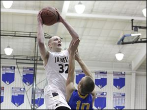 Perrysburg player Matt Schimmoeller (32) shoots over Findlay player Kyle Boyd (10).