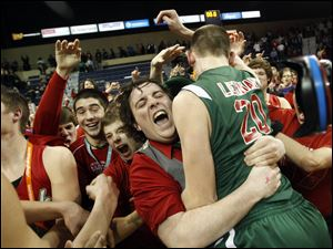 Central Catholic senior Devon Desmond hugs Drew Lehman (20) as students mob the players in celebration after defeating St. John's in their Division I district final at the University of Toledo.