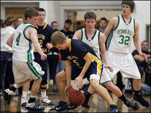 Toledo Christian's Eric Cellier (5) recovers a loose ball from  Ottawa Hills' Logan Glosser (4) during the Division IV boys district final. The Eagles won 48-31.
