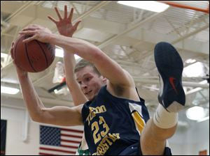 Toledo Christian's David Westmeyer (23) pulls in a rebound against Ottawa Hills.