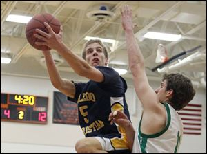 Toledo Christian's Eric Cellier (5) goes to the net against  Ottawa Hills'  Andrew Jamieson (11).