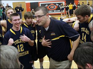 Toledo Christian coach David McWhinnie congratulates  his team for winning the Division IV boys district final against Ottawa Hills.