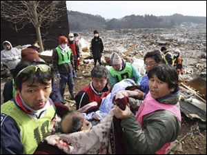 Rescue workers carry an elderly man found alive by tsunami survivors buried under rubble along a slope of a hill in Minamisanrikucho in Miyagi Prefecture on Monday, three days after a powerful earthquake-triggered tsunami hit the country's northeast coast.