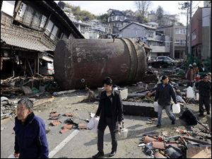 People walk through a street covered in rubble Monday to receive water in Kesennuma, Miyagi Prefecture, northern Japan.