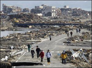 People walk a road between the rubble of destroyed buildings in Minamisanriku town, Miyagi Prefecture, northern Japan, on Monday, three days after a powerful earthquake-triggered tsunami hit the country's east coast.