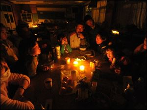 Evacuees gather around the candlelight at a blacked out shelter Monday in Yamamoto, Miyagi Prefecture, northern Japan.
