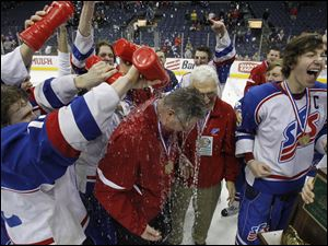 Toledo St. Francis de Sales players dump water over head coach Brian Kinsella, center, at Nationwide Arena after winning the state title.