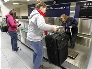 tElizabeth Romuald, left, checks in for Delta's last flight from Toledo Express while her sister Anna, who was seeing her off to Minneapolis, lifts her bag onto the scale.