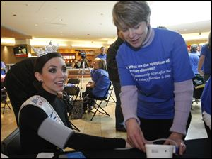 Becky Minger, 23, of Sylvania, who is Miss Ohio 2010, has her blood pressure checked by Kidney Foundation volunteer Debbie Mills.