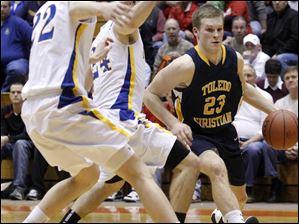 Toledo Christian's David Westmeyer dribbles past Continental's  Austin Sharp (24), and John Spitnale (22).