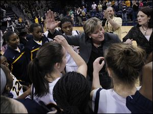 Toledo head coach Tricia Cullop is surrounded by her team after they defeated Delaware 58-55.