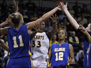 Rockets' Yolanda Richardson (33) passes a ball through the hands of Delaware's Elena Delle Donne (11) and another teammate.
