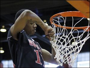 Rogers' Damond Powell cuts down the net after the Rams beat Rocky River High during their Division II Regional final.