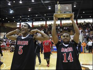 Rogers players Markeith Douglas (5) and Brandon Hunt (10) display the their trophy to fans.