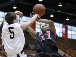 Rogers' Damond Powell (11) is fouled by Rocky River's Jimmy Corrigan.