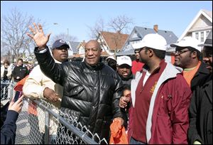 Bill Cosby waves to people on their porches as he walks down Woodland Drive in central Toledo. The comic used wit to lighten his words on keeping the streets safe for children and the elderly.