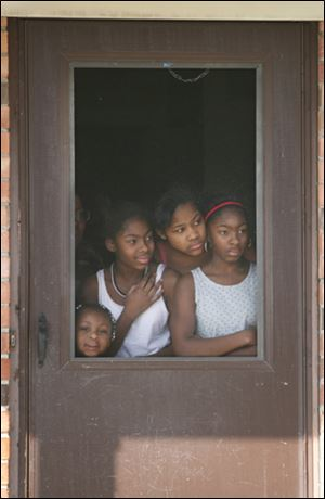 Jacheyla Smith 3, left, Kim McHaney, 12, Kiana McHaney 12, and Appalonia McHaney, 15, watch Bill Cosby arrive at Martin Luther King, Jr., school. Mr. Cosby, who has a PhD in education, encouraged boys inside  to get their parents involved in school.