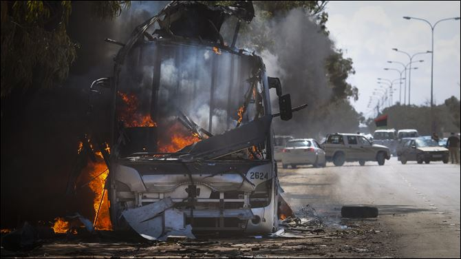 A bus burns on a road leading to the outskirts of Benghazi, eastern Libya, though it's not clear how or who destroyed it.