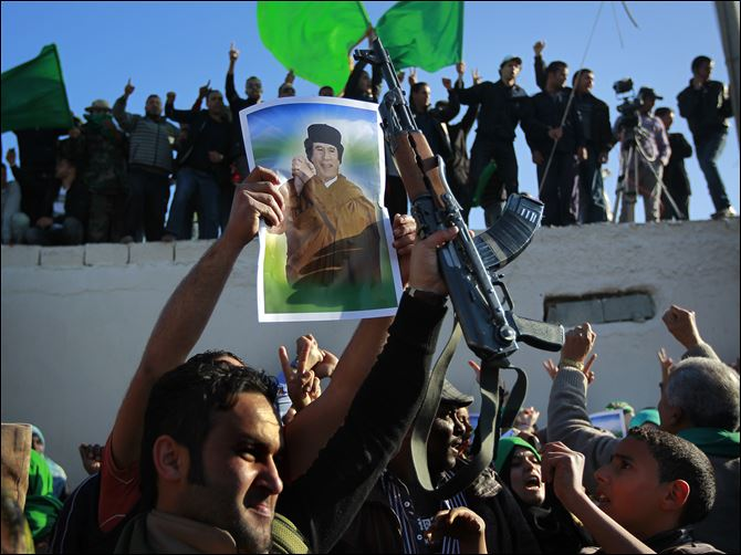 In  an organized trip by the Libyan authorities, people demonstrate their support for Libyan leader Moammar Kaddafi as they wait for the bodies of 26 people said to be killed during overnight air raids to arrive for burial in Tripoli Sunday.