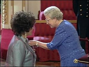 Dame Elizabeth Taylor receives the honour of Dame Commander of the Order of the British Empire from Britain's Queen Elizabeth II, right, in this image taken from video during a ceremony held at Buckingham Palace, in London on May 16, 2000. The award was given in recognition for Taylor's services to the entertainment industry and to charity.