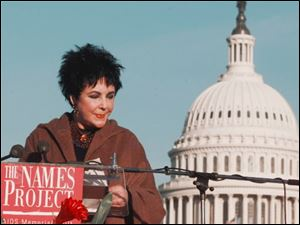 Actress Elizabeth Taylor reads aloud some of the thousands of names of people who have died from AIDS at an event Oct. 12, 1996 in front of the U.S. Capitol in Washington.