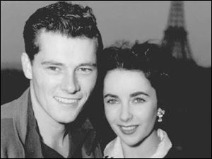 Actress Elizabeth Taylor poses with her new husband, hotel heir Nick Hilton, as they stand on the terrace of their hotel room in Paris while on their honeymoon in this May 31, 1950 file photo.