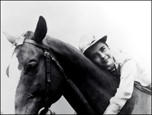 Young actress Elizabeth Taylor hugs the neck of her horse in