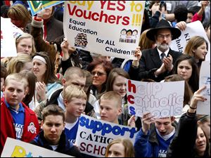 A rally at the Statehouse in Columbus draws more than 1,000 to show support for Gov. John Kasich's proposal to quadruple the number of school vouchers.