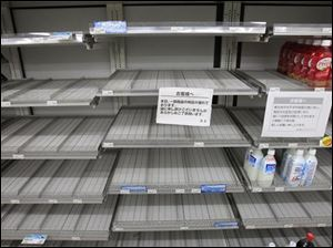 Shelves selling bottled water are empty at a convenience store in Tokyo Wednesday.