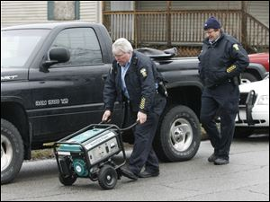 Toledo Police take possession of a portable generator at 1319 Hamilton St. in central Toledo where a mother and three children were found dead in the living room.