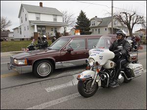 Sandusky motorcycle police escort slain Sandusky police officer Andrew Dunn during the procession from The Chapel to the Calvary Cemetery Mausoleum in Sandusky, Ohio.