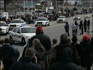 Toledo police cars participate in the procession from The Chapel to the Calvary Cemetery Mausoleum.