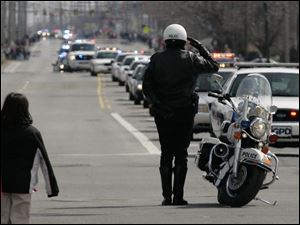 A motorcycle police officer salutes the Andrew Dunn procession.