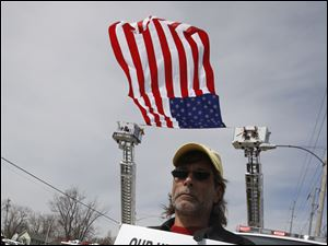 Sandusky resident Mark Weikle watches the Andrew Dunn procession from The Chapel to the Calvary Cemetery Mausoleum in Sandusky, Ohio. In the background is a giant American flag help up by firetruck ladders.