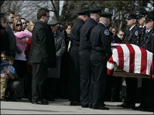 Cleveland honor guard give a three-volley salute for slain Sandusky police Officer Andrew Dunn at the Calvary Cemetery Mausoleum.