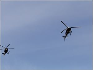 Helicopters fly over the service at Calvary Cemetery Mausoleum.
