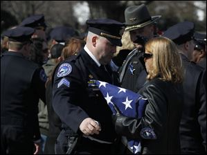 Sandusky police Sgt. R.E. Snyder hugs a family member of  slain Sandusky police Officer Andrew Dunn after the service at Calvary Cemetery Mausoleum in Sandusky, Ohio.